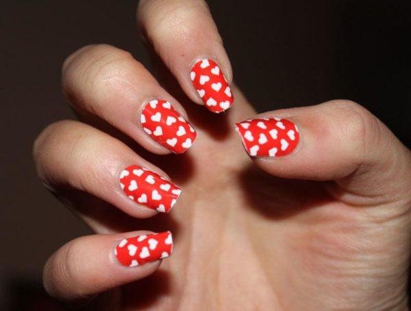 unas-decoradas-para-el-dia-de-san-valentin-corazones-blancos-sobre-fondo-rojo