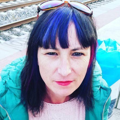 Mujer con morena con pelo por los hombros y flequillo con mechas azules