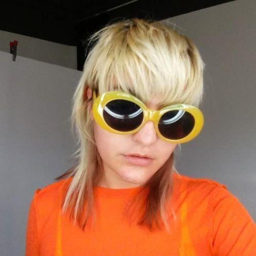 Muchacha corte a capas moderna con gafas de sol amarillas