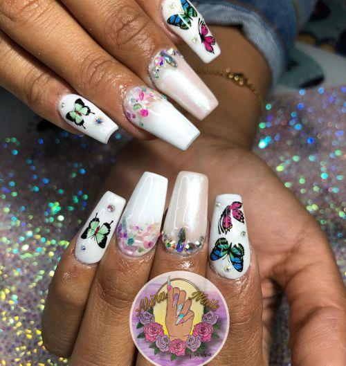 Uñas blancas con decoraciones de mariposas