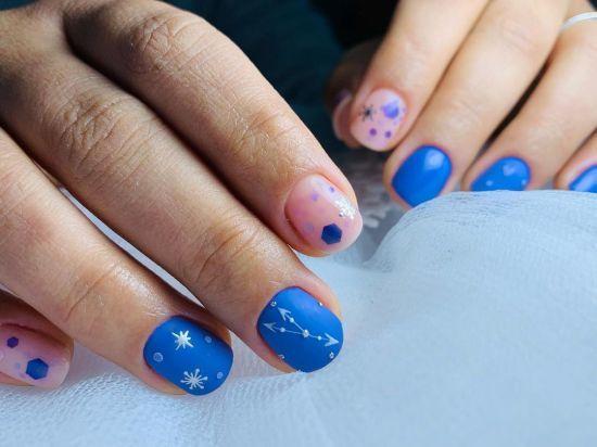 Uñas en azul con símbolos en blanco