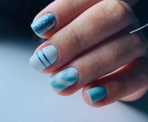 Uñas cortas azules y blancas con franjas