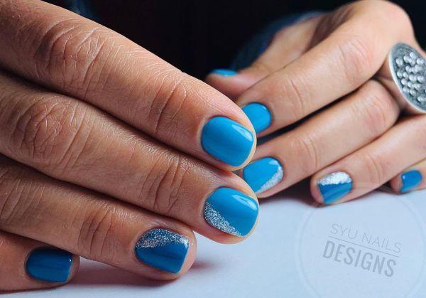 Uñas azules con brillo salpicado en los laterales