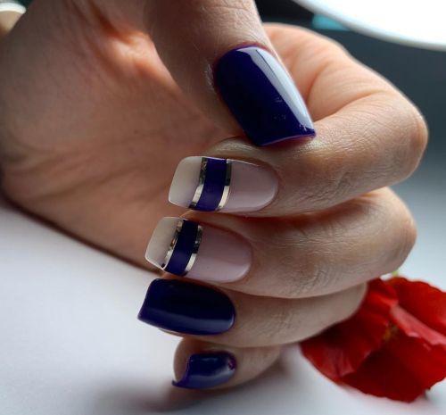 Uñas azul marino con rosa palo y aros de plata y azul