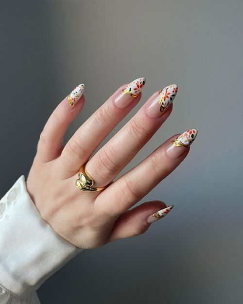 Uñas largas con anillo de oro y flores
