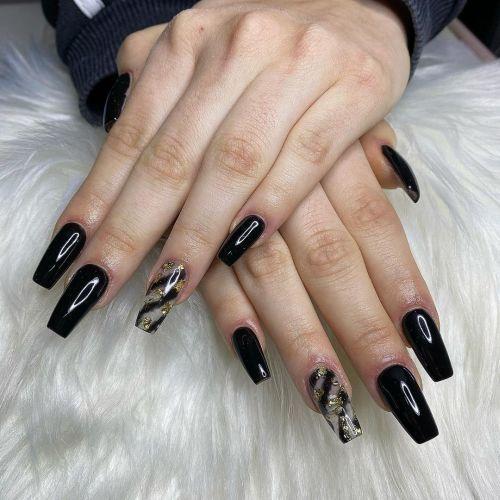 Uñas negras con transparente de rayas y dorado