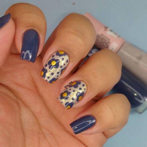Uñas azul eléctrico con flores lilas y amarillo