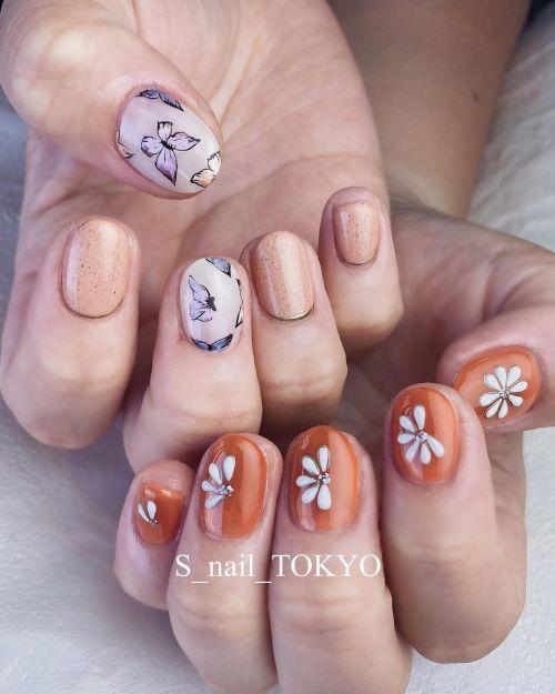 Uñas con flores y fondo en tonos marrón