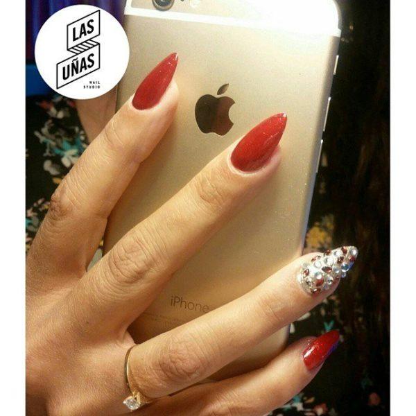 Uñas rojas en forma oval con una uña en plateado y con piedras