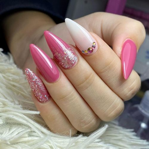Uñas largas y en punta rosa con brillo y dibujo