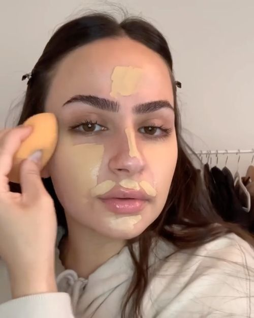 Joven aplicando base de maquillaje