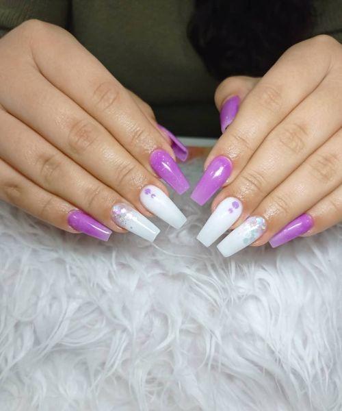 Uñas largas moradas con blancas y adornos morados