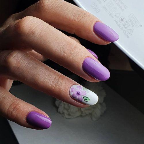 Uñas moradas con uña blanca y flor