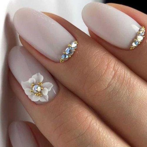 Uñas blancas de boda con flores y perlas doradas