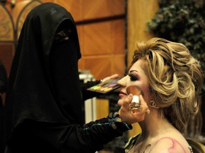 A Saudi woman applies makeup on a model