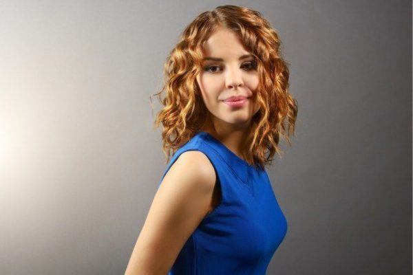 Pretty girl with short curly hair on light background