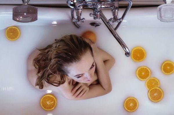 productos-y-remedios-caseros-para-el-pelo-graso-mujer-en-la-ducha-naranjas